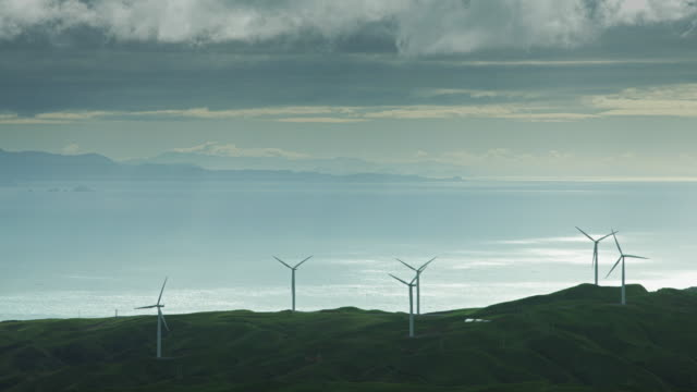 Wind Turbines Silhouetted Against Shining Sea