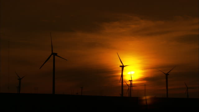 WS Wind turbines silhouetted against sunset sky, Huitengxile, Inner Mongolia, China