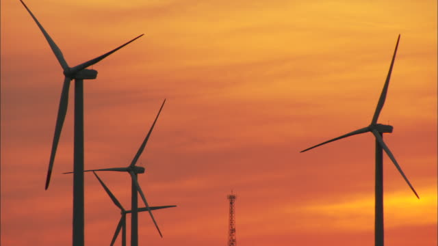 MS Wind turbines silhouetted against sunset sky, Huitengxile, Inner Mongolia, China