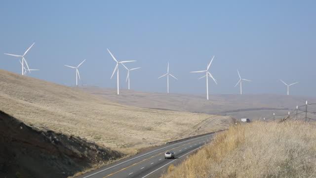 turbine eoliche girano sopra le colline, strada - on the move video stock e b–roll