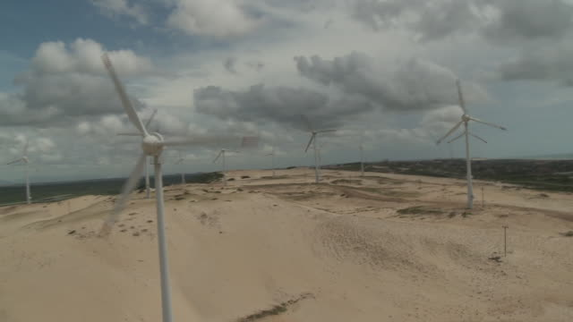 Wind turbines spin across sand dunes in Fortaleza, Brazil.