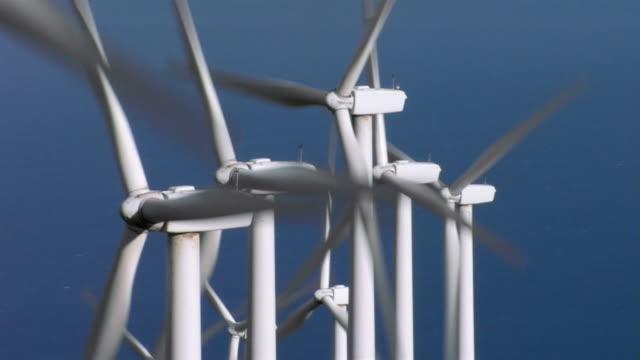 Wind turbines spin against a blue sky in North Dakota.