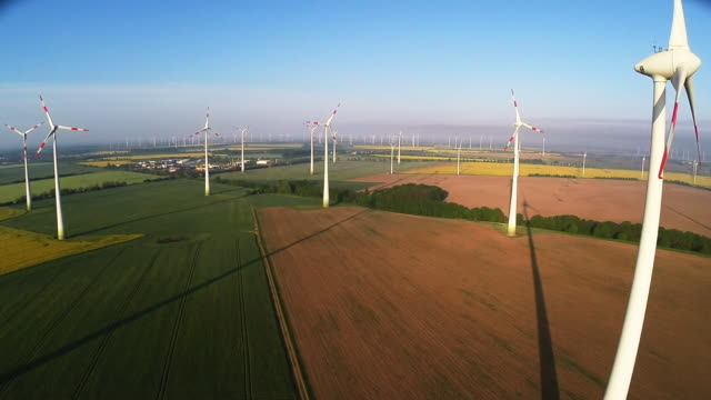 wind turbines spin at a wind farm on may 15, 2015 near brieselang, germany. germany is extricating itself from nuclear energy and raised its goals... - nuclear energy点の映像素材/bロール