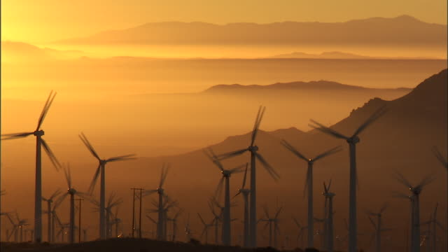 wind turbines spin at sunrise. - windmill stock videos & royalty-free footage