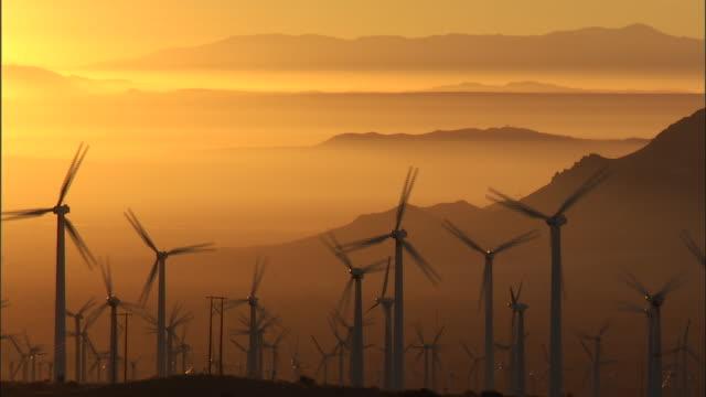 wind turbines spin at sunrise. - wind turbine stock videos & royalty-free footage
