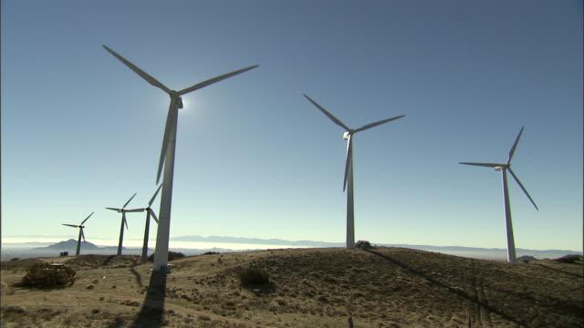 wind turbines spin in a dry field. - 風力発電機点の映像素材/bロール