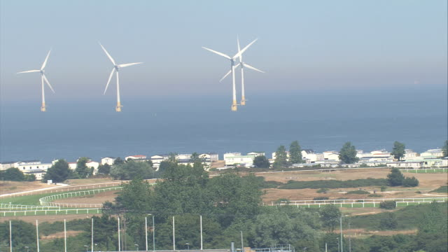 wind turbines spin off the british coastline. available in hd. - turbine stock videos & royalty-free footage