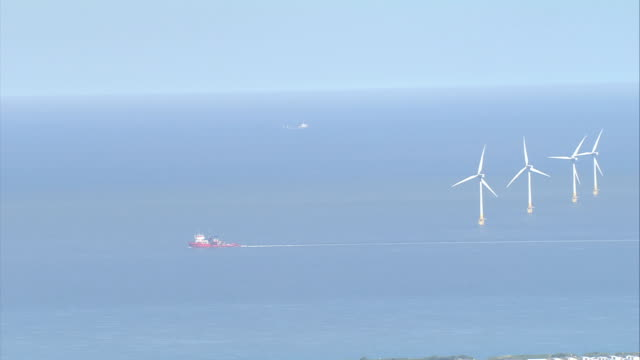 Wind turbines spin off the coast of Britain. Available in HD.