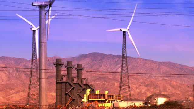 wind turbines spinning blades next to modern natural gas fired electric power plant with smoke stacks polluting the air / Palm Springs, California, USA
