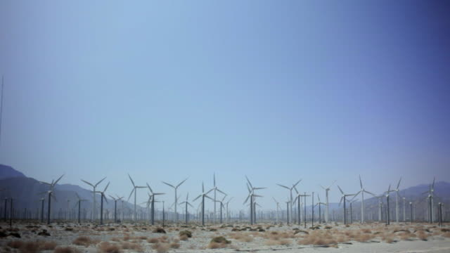 WS Wind turbines spinning in desert, mountain in background / Palm Springs, California, USA