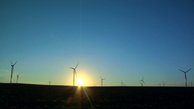 WS Wind turbines spinning in field with sun behind them/ Kewaunee, Illinois