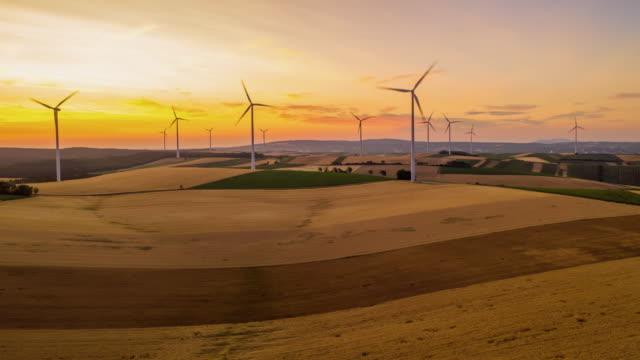 vídeos de stock, filmes e b-roll de turbinas de vento de h/l que giram no campo no crepúsculo - ensolarado