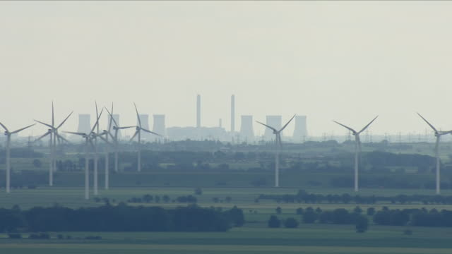 wind turbines with a coal power plant in background - coal stock videos & royalty-free footage