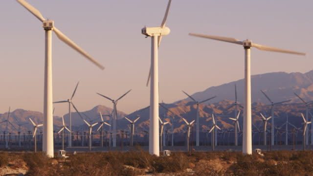 ls wind turbines with mountains in background / palm springs, california - wind turbine stock videos & royalty-free footage