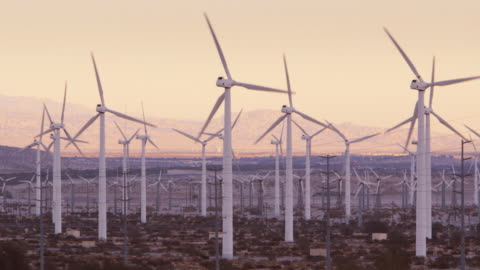 ls wind turbines with mountains in background / palm springs, california - 風力発電点の映像素材/bロール