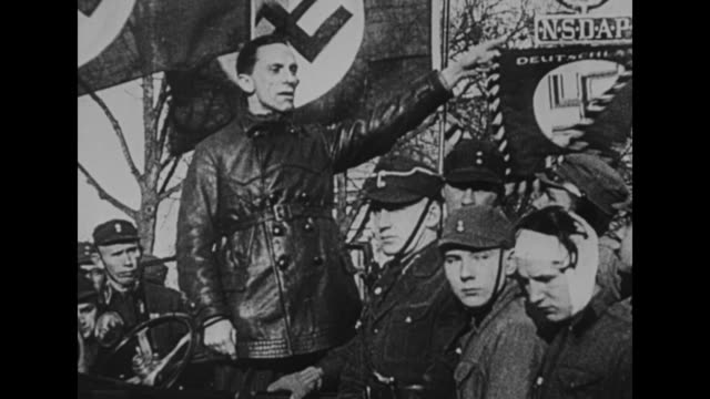 Wind whips Nazi flags behind Joseph Goebbels as he stands in a car and makes a speech man with bandaged head stands nearby / arms of people in crowd...