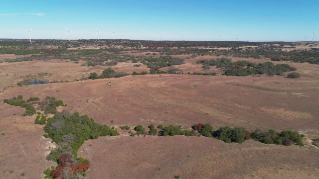 windfarm on the horizon in the savanna grassland, arid highland in texas, usa. aerial drone video with the forward camera motion. - plain stock videos & royalty-free footage