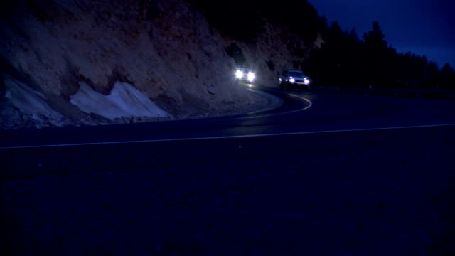 winding bending highway along cliff side various vehicles approaching passing in both directions bright headlights ca - approaching stock videos & royalty-free footage