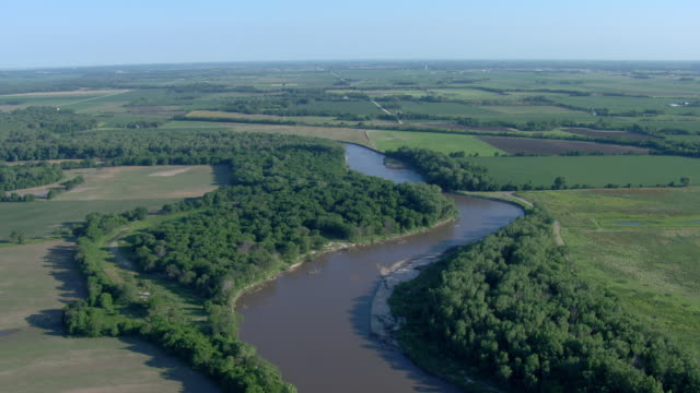 Winding river surrounded by trees and fields