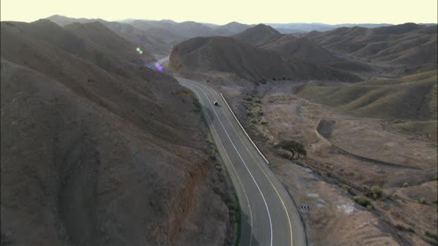 aerial winding road crossing judea desert, israel - winding road stock-videos und b-roll-filmmaterial