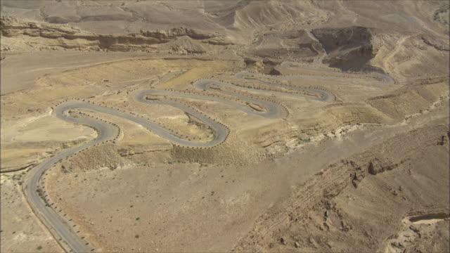 aerial ws winding road in desert, negev, israel - winding road stock-videos und b-roll-filmmaterial