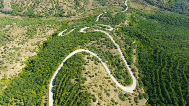 aerial: winding road through hilly terrain with forests - lush stock videos & royalty-free footage