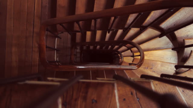 kurvenreiche spirale hölzerne treppe dezoom - treppe stock-videos und b-roll-filmmaterial