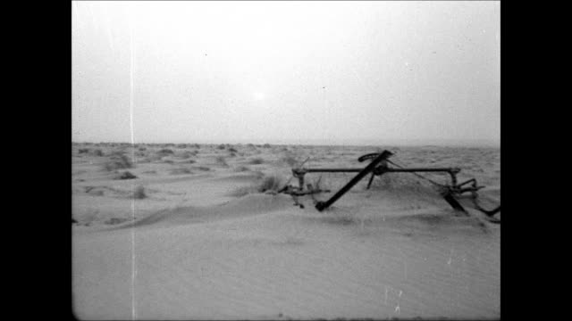 vidéos et rushes de windmill blades amp 'thomas texas' fin ws dried land w/ patches of scrub amp farm equipment partially covered in sand sand dunes windswept up around... - tempête de poussière