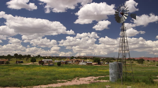 Windmill on New Mexico field under cloudy sky, wide shot