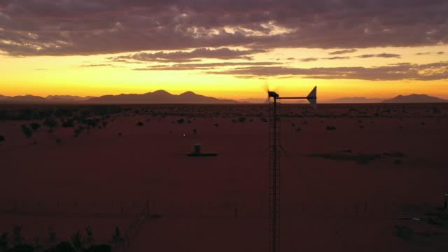 vidéos et rushes de ws windmill tournant au-dessus du paysage de désert au coucher du soleil, namibie, afrique - dune de sable