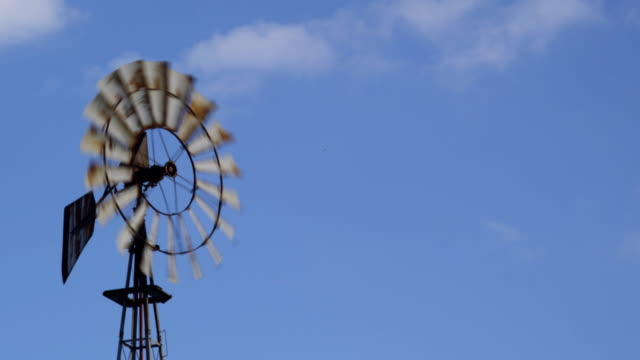 Windmill spinning under a blue sky with some clouds