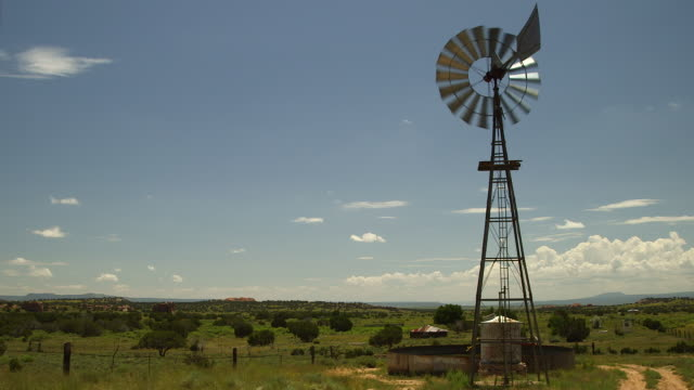 vídeos de stock, filmes e b-roll de windmill spins in new mexico field under clear sky, wide shot - moinho