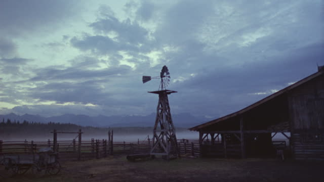 A windmill stands next to an old, weathered barn.