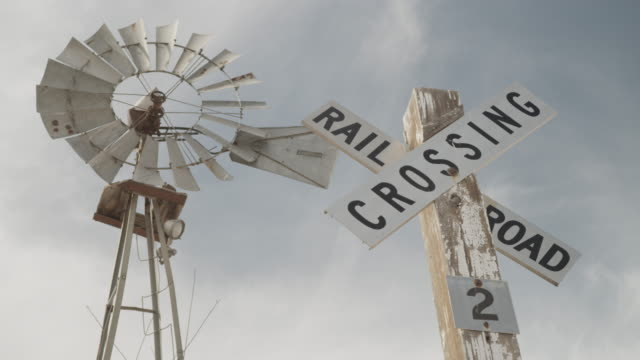 Windmill sways in breeze next to railroad crossing sign