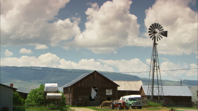 A windmill towers above buildings and vehicles on a farm.