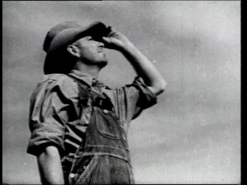 stockvideo's en b-roll-footage met windmill turns / farmer looks to sky / dust dervish on dry ground / outdoor light swinging on wires - 1936