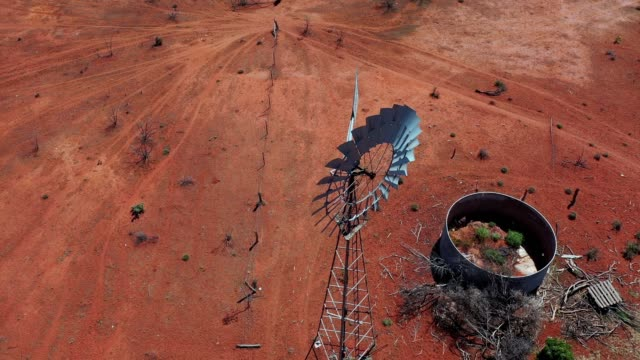 windmill, water windpump on farm with dry red dirt field, australia, aerial view - drought stock videos & royalty-free footage