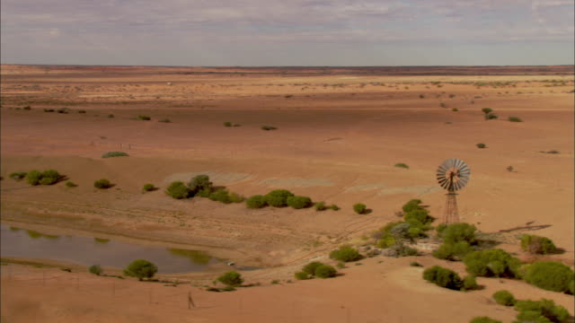 vídeos de stock, filmes e b-roll de aerial windmill with few scattered plants and empty water hole, anna creek station, south australia, australia - caldeirão água parada