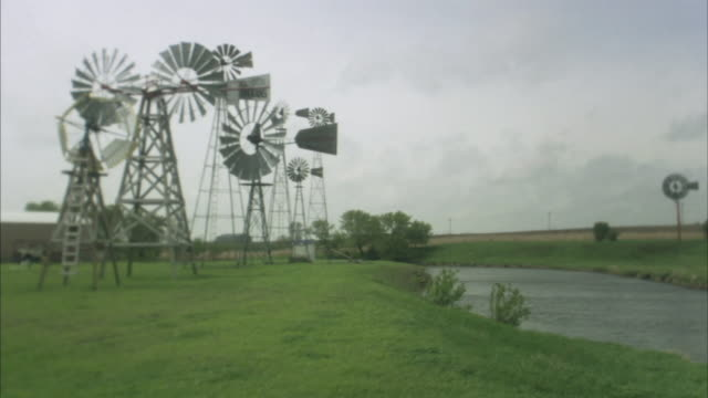 ws windmills next to river with train passing in background/ buffalo ridge, minnesota - medium group of objects stock videos & royalty-free footage