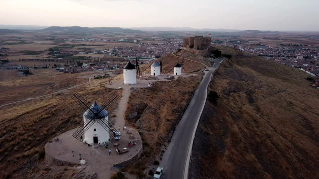 windmills on hill at sunset in consuegra, mancha, spain. aerial view - spagna video stock e b–roll