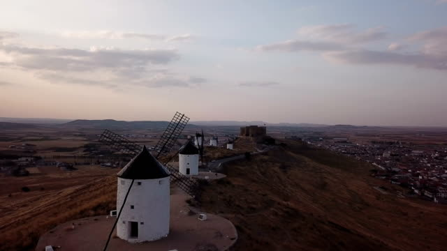 Windmills on hill at sunset in Consuegra, Mancha, Spain. Aerial view