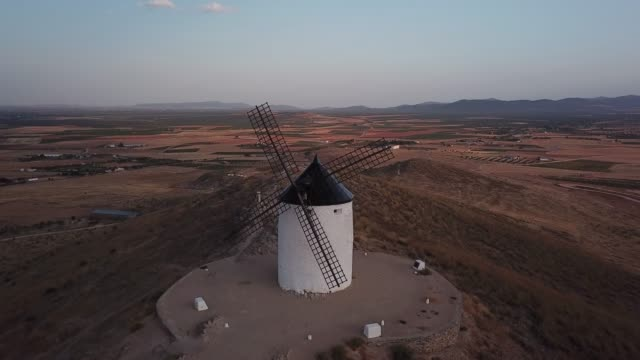 windmills on hill at sunset in consuegra, mancha, spain. aerial view - castello video stock e b–roll