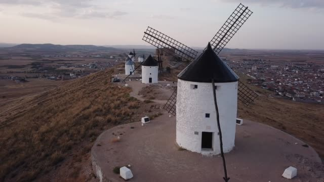 windmills on hill at sunset in consuegra, mancha, spain. aerial view - スペイン点の映像素材/bロール