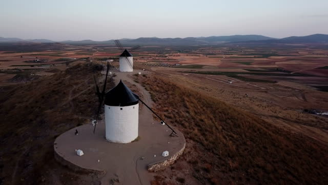 windmills on hill at sunset in consuegra, mancha, spain. aerial view - plateau stock videos and b-roll footage