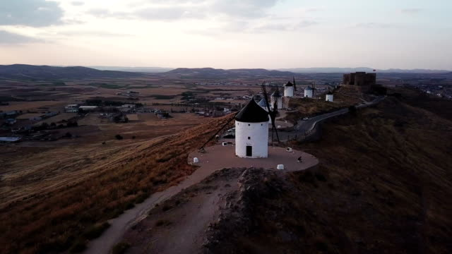 vidéos et rushes de windmills on hill at sunset in consuegra, mancha, spain. aerial view - spain