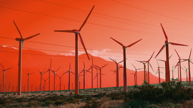 T/L WS Windmills spinning against orange mountains and sky / Palm Springs, California, USA