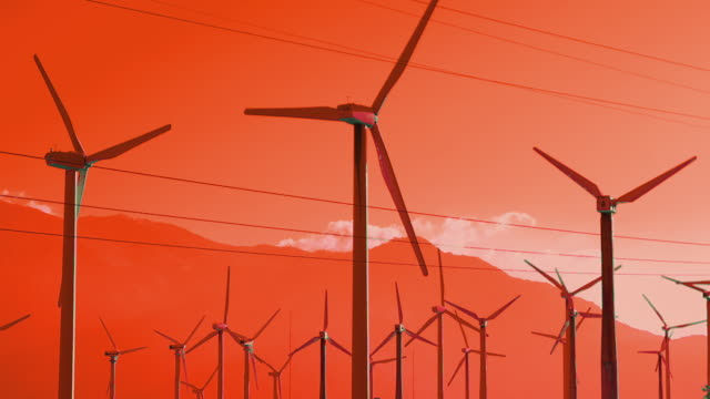 T/L MS Windmills spinning against orange mountains and sky / Palm Springs, California, USA