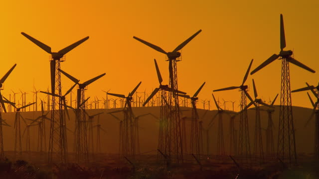 vidéos et rushes de t/l ws pan windmills spinning against sky at sunset / palm springs, california, usa - image teintée