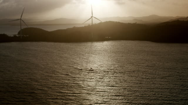 WS AERIAL POV Windmills spinning in coastline / Naguabo, Puerto Rico, United States