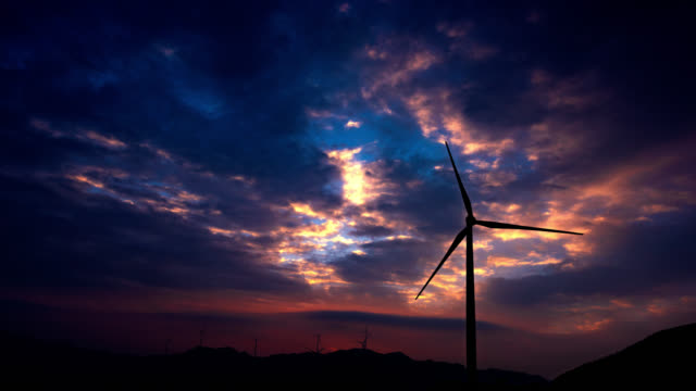 windmills turbine sunglow at sunrise 4k uhd - propeller stock videos & royalty-free footage